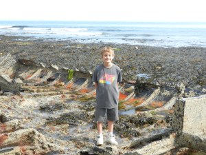 Boy playing in tidal pools in shipwreck